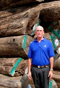 Gib McIlvain beside a pile of Teak logs