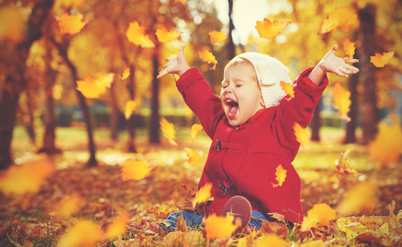 child playing with fall leaves