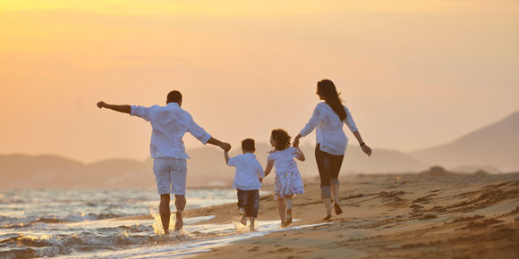 family walking along ocean shore