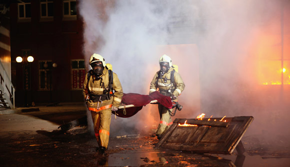 firemen with body from burning building