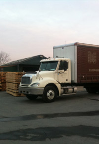 J Gibson McIlvain truck by stacked wood