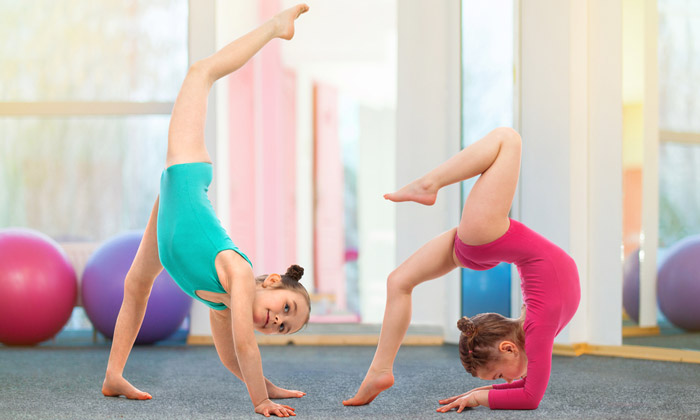 two young girls practicing in gymnastics class