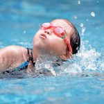 young swimmer girl working on breathing while swimming
