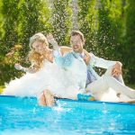 bride and groom splashing by pool