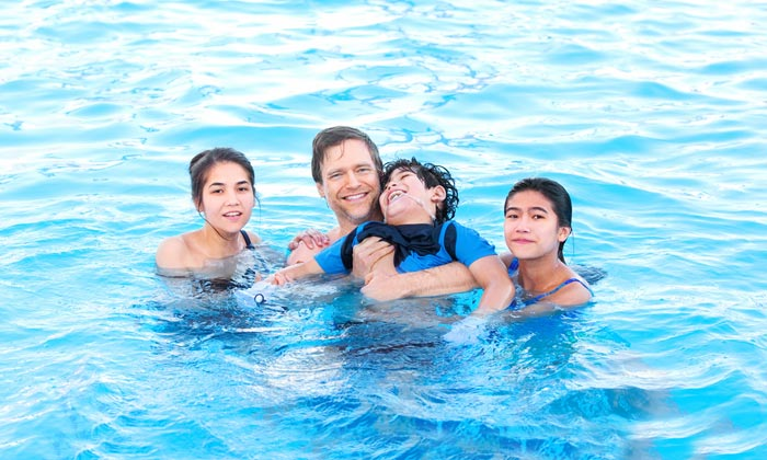 family with child with disability in pool