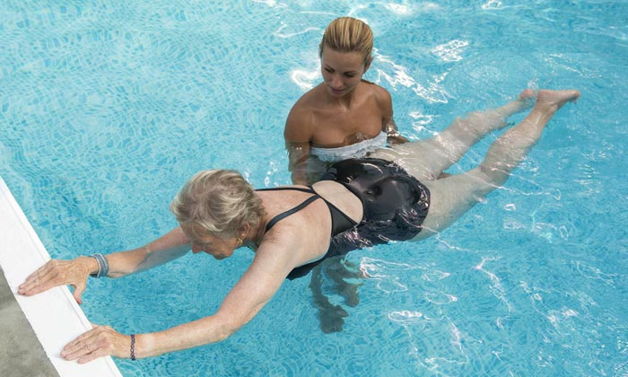 woman assisting elderly lady in pool