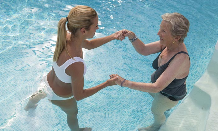 young lady assisting elderly woman in pool