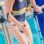 helping young woman with disability at pool