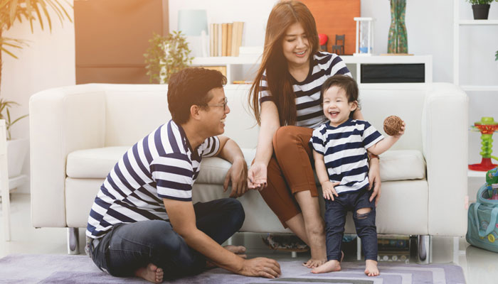 happy mom and dad with young smiling child