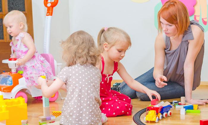 daycare teacher on floor with three children