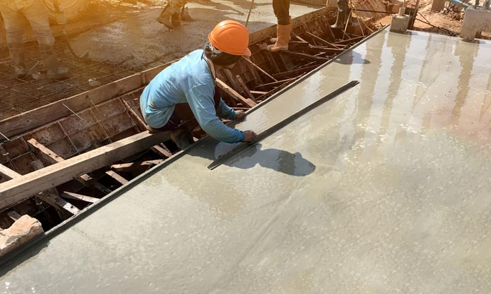 worker smoothing liquid concrete