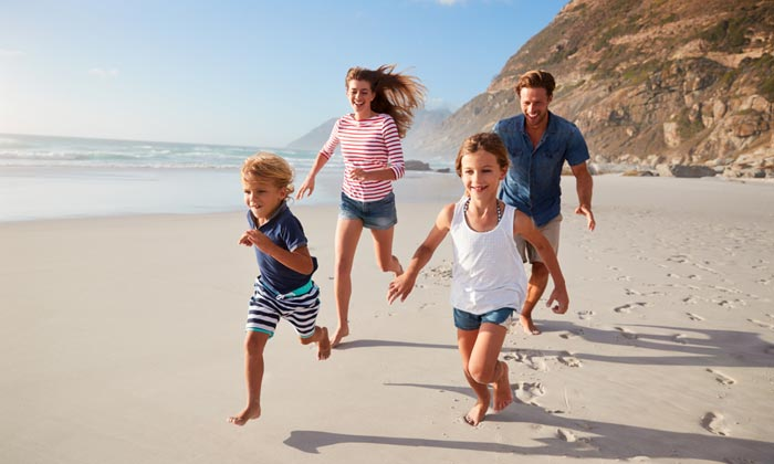 parents running on beach with kids