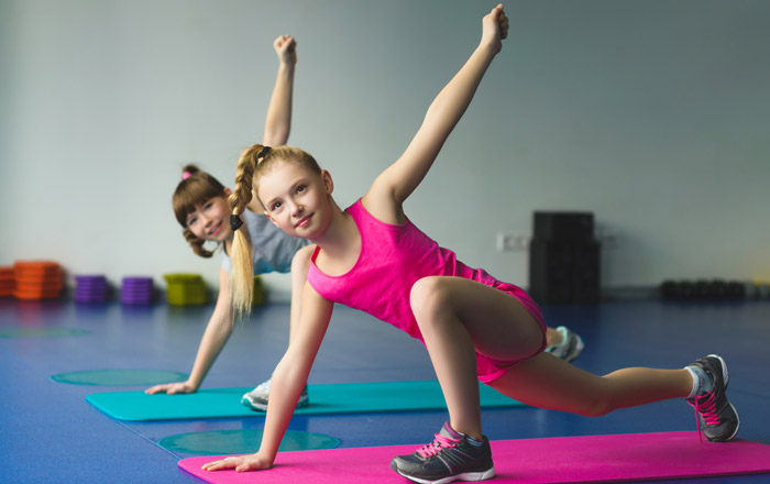 girls stretching gymnastics on mats