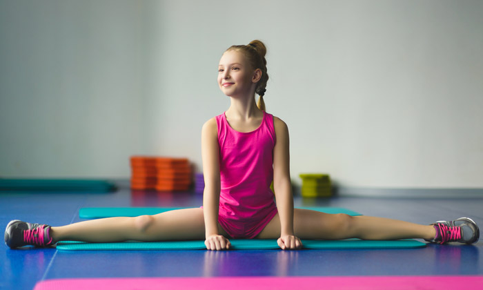 preteen girl doing leg stretch on gymnastic mat