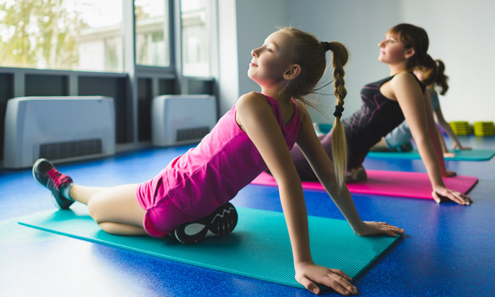 two girls on mats practicing gymnastics moves