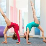 two gymnastic young girls demonstrating moves