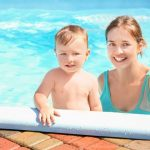 mom with young boy in pool water