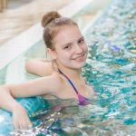 teenage girl relaxing in pool water