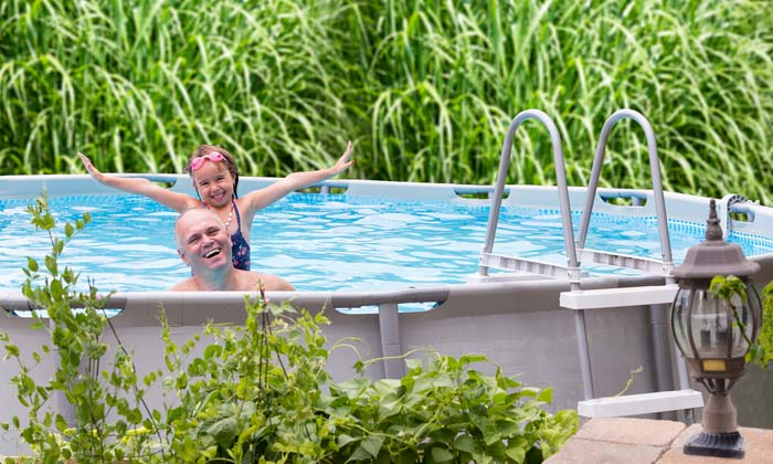 father and daughter excited to be in backyard pool