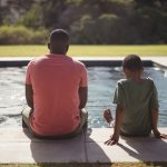 father and son sitting beside pool
