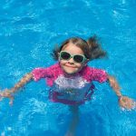 young girl smiling from pool