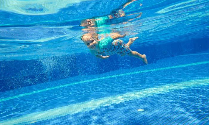 young child swimming underwater