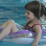 young girl floating on pool water