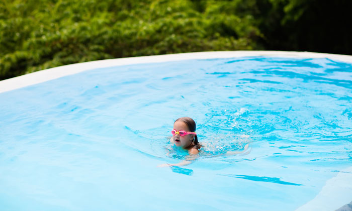 girl with goggles having fun in pool