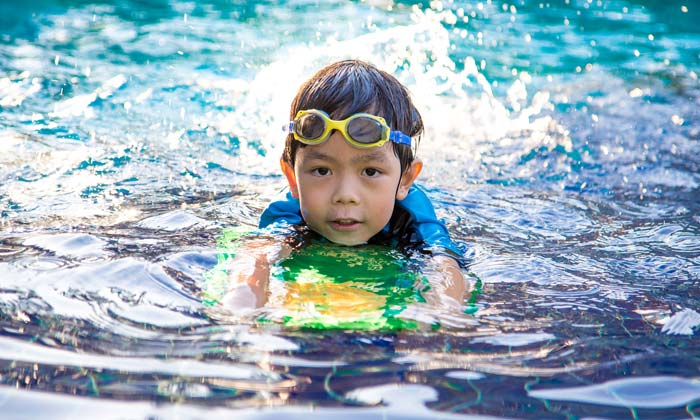 boy with goggles learning to swim