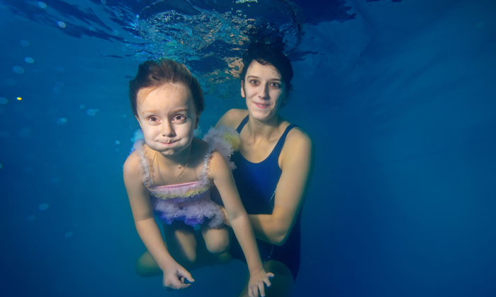 mom holding young girl underwater