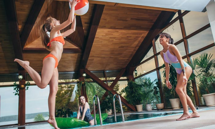 young women playing with ball by pool