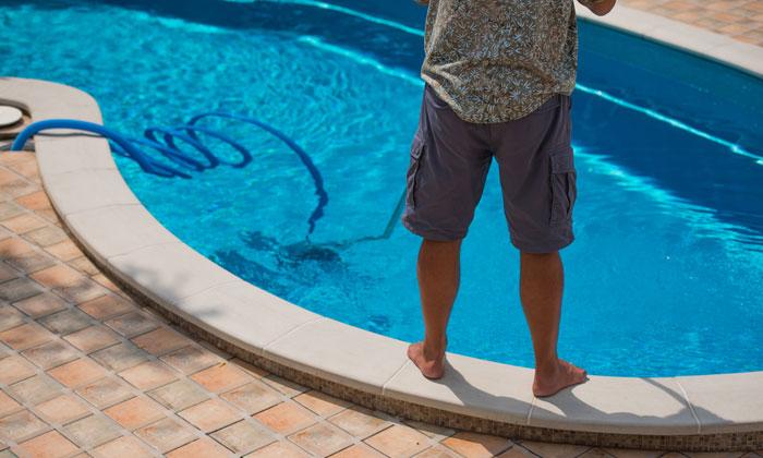 man vacuuming the bottom of his swimming pool
