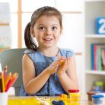 cute preschool girl playing with modeling dough