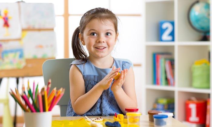 cute preschool girl playing with modeling dough