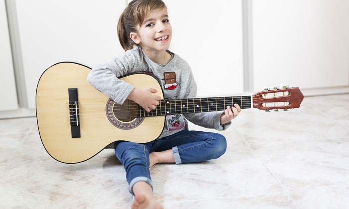 young girl taking guitar music lessons