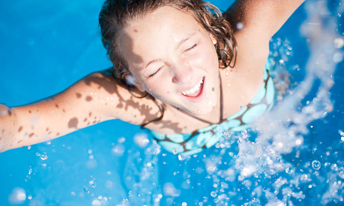 excited young woman swimming in pool
