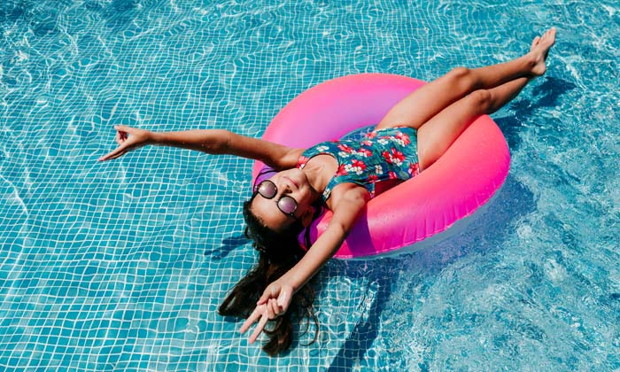 girl floating on pink pool tube