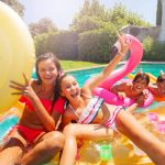 group of preteen friends on floats in pool