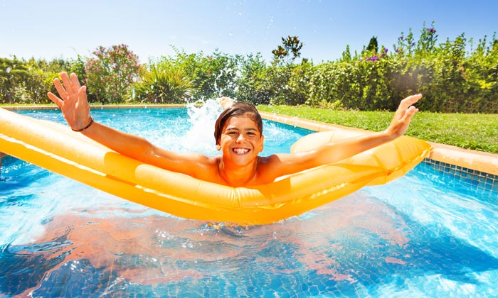 teen boy on raft in swimming pool