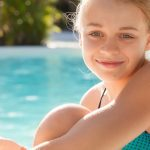 teen girl grinning sitting beside pool edge
