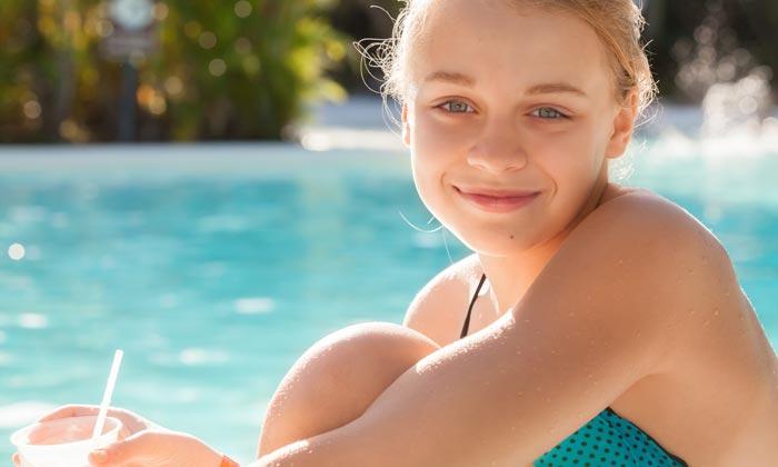 teen girl grinning sitting beside pool edge