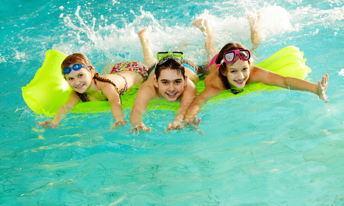three teens floating on pool raft