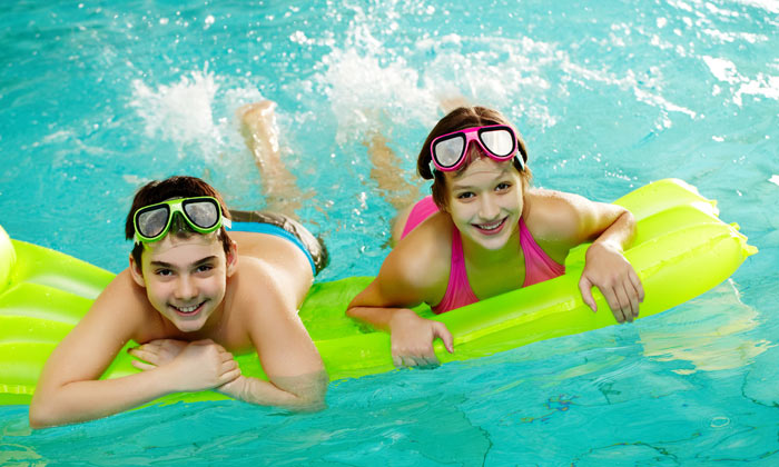 two teens happy swimming in water pool