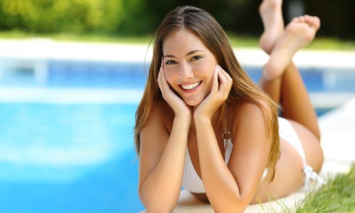 young woman in bikini lying at edge of pool