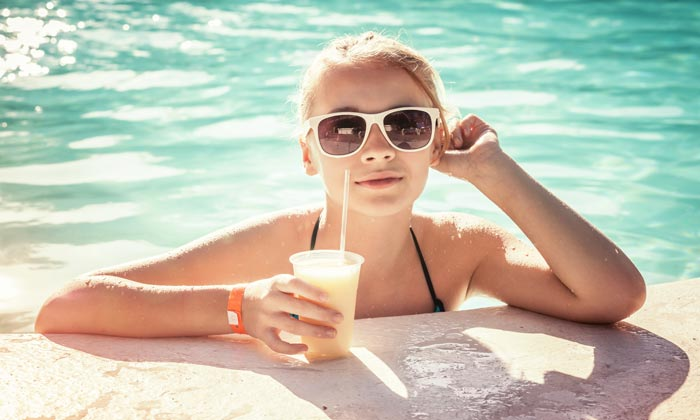 young woman with shades and cold drink in pool