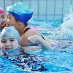 children in swim school learning how to swim