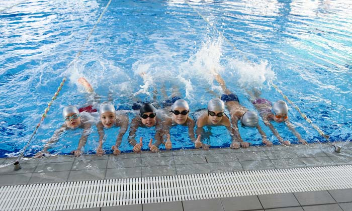 group of swim lesson students kicking water