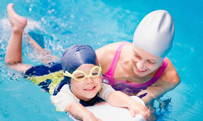 swim instructor helping young boy student