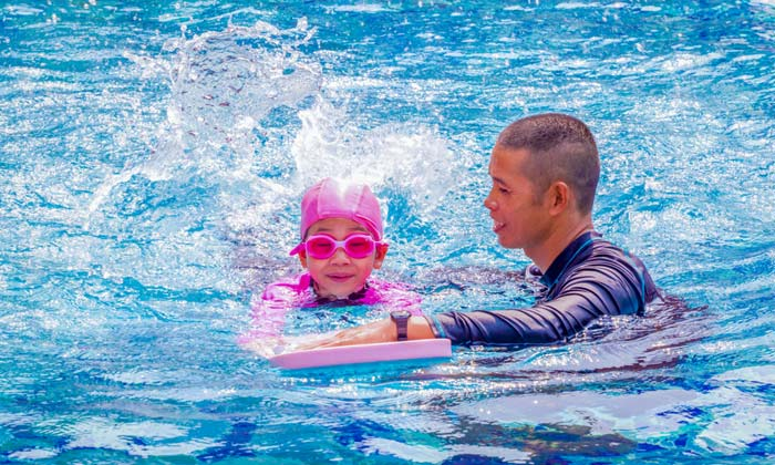 swim instructor helping young goggle child learn to swim