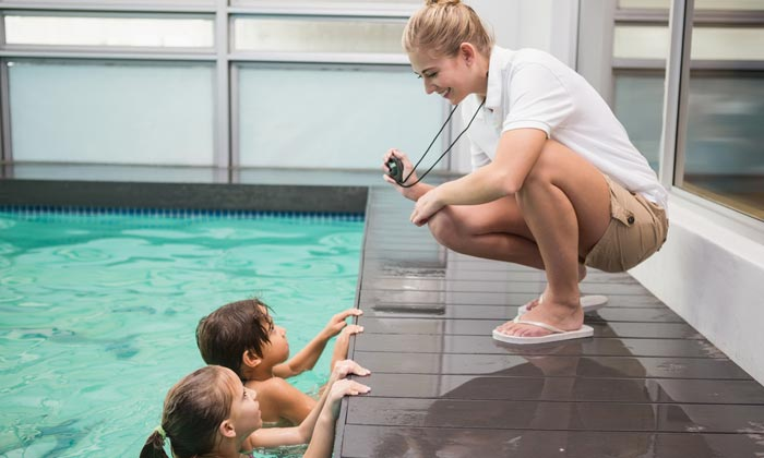 swim instructor prepares to time students lap
